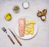 Gerookte vissen, met aardappels en dille op een witte plaat, met dicht omhoog kruiden, mes en vork houten hoogste mening rustieke stock afbeeldingen