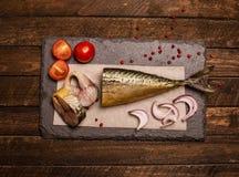 Gerookte vissen met ui, tomaat en peper De achtergrond van het voedsel Royalty-vrije Stock Foto's
