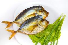 Gerookte vissen op witte plaat met groenten op backgroun Stock Afbeelding