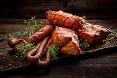 Gerookte vlees en worsten Een reeks traditionele gerookte vlees en worsten: ham, gerookte ham, varkensvleeslendestuk, huis-stijl  royalty-vrije stock afbeelding