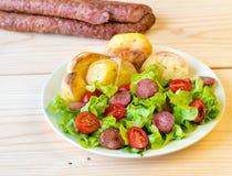 Gerookte worst met groentensalade op een houten raad Royalty-vrije Stock Afbeeldingen