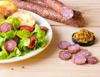 Gerookte worst met groentensalade op een houten raad Royalty-vrije Stock Foto