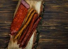Gerookte worsten op de textuur van hout, op een houten achtergrond, vrije ruimte voor tekst, daglicht Stock Foto