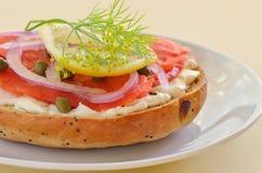 Gerookte zalm lox op Asiago kaasongezuurd broodje Stock Foto