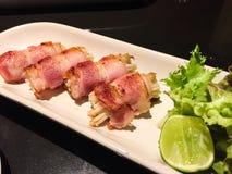 Geroosterd Bacon met Gouden Naaldpaddestoel Dit is een voorgerecht met verse salades en kalk royalty-vrije stock afbeelding