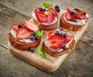 Geroosterd brood met bessen en roomkaas stock afbeeldingen