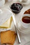 Geroosterd brood met boter, jam en thee stock afbeeldingen