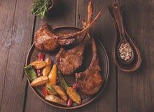 Geroosterd de ribbenlendestuk van het lamskalfsvlees met groenten op een plaat Stock Foto's