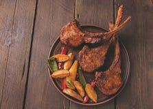 Geroosterd de ribbenlendestuk van het lamskalfsvlees met groenten op een plaat Stock Fotografie
