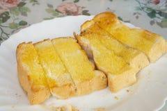 Geroosterd die brood met geel boterbovenste laagje in een witte ceramische schotel op de lijst voor een ontbijt wordt gesneden royalty-vrije stock foto
