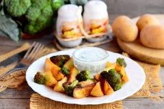 Geroosterd groentenidee Geroosterde aardappelsplakken en broccoli met saus op een witte plaat en een houten lijst Stock Fotografie