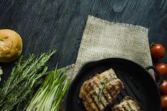 Geroosterd lapje vlees op een ronde die grillpan, met kruiden voor vlees, rozemarijn, greens en groenten op een donkere houten ac stock afbeeldingen