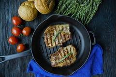 Geroosterd lapje vlees op een ronde die grillpan, met kruiden voor vlees, rozemarijn, greens en groenten op een donkere houten ac royalty-vrije stock fotografie