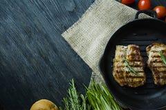 Geroosterd lapje vlees op een ronde die grillpan, met kruiden voor vlees, rozemarijn, greens en groenten op een donkere houten ac royalty-vrije stock afbeeldingen