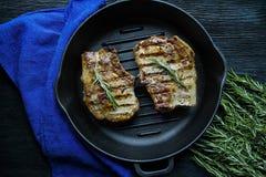 Geroosterd lapje vlees op een ronde grillpan, die met kruiden voor vlees, rozemarijn op een donkere houten achtergrond wordt verf stock afbeelding