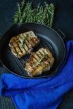 Geroosterd lapje vlees op een ronde grillpan, die met kruiden voor vlees, rozemarijn op een donkere houten achtergrond wordt verf royalty-vrije stock afbeeldingen