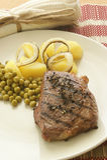 Geroosterd peperlapje vlees met aardappel en erwt stock afbeelding