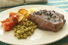 Geroosterd peperlapje vlees met geroosterde aardappel en erwt Stock Afbeeldingen