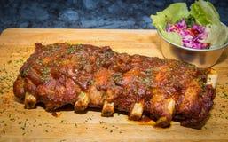 Geroosterd ribvarkensvlees met barbecuesaus en groente op houten scherpe raad Stock Foto's