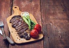 Geroosterd rundvleeslapje vlees met asparaguas en tomaten op een houten rustieke achtergrond stock afbeelding
