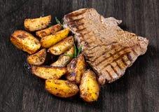 Geroosterd Rundvleeslapje vlees met Gebakken op de aardappels van het Grilldorp, rozemarijn op houten oude raad Achtergrond, Text stock fotografie
