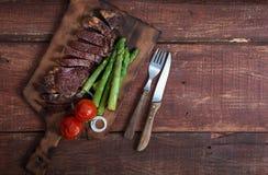 Geroosterd rundvleeslapje vlees met groenten op een houten rustieke achtergrond, met exemplaarruimte stock afbeeldingen