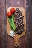 Geroosterd rundvleeslapje vlees op een lichte hakbord houten rustieke achtergrond stock foto's