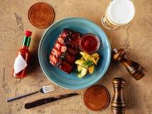 Geroosterd striploin gesneden lapje vlees en bier over steenlijst stock foto's