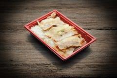 Geroosterd varkensvleesbovenste laagje op Japanse rijst in plastic dienblad stock afbeeldingen