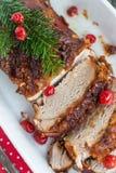 Geroosterd varkensvleeslendestuk met kersen en kruiden op feestlijst Stock Foto