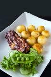 Geroosterd vlees met gebraden aardappels en plantaardige salade Royalty-vrije Stock Foto's
