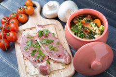 Geroosterd vlees met groenten in een pot en een vers varkensvleeshaasbiefstuk Royalty-vrije Stock Foto's
