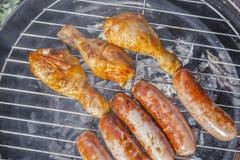 Geroosterd worsten en van kippenbenen close-up op de grill stock afbeeldingen
