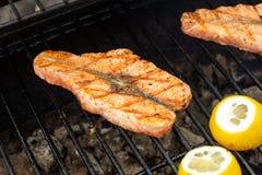 Geroosterd zalmlapje vlees op het vlammen en de citroen royalty-vrije stock foto's