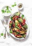 Geroosterde aubergine met feta, Griekse yoghurt, koriandersaus en granaatappelzaden op lichte achtergrond, hoogste mening Heerlij royalty-vrije stock fotografie