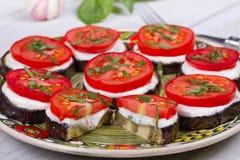 Geroosterde aubergine met kruidige zure roomsaus, tomaten en basilicum Stock Afbeeldingen