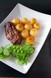 Geroosterde biefstuk, aardappelen in de schil en groenten royalty-vrije stock foto's
