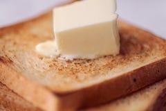 Geroosterde broodplakken met kluit boter voor ontbijt Stock Foto's