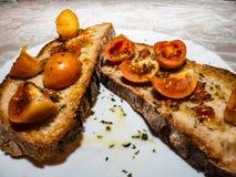 Geroosterde bruschetta met Italiaanse tomaten, oranje kleur, zeer goed en durend, kruidde met olijfolie royalty-vrije stock fotografie