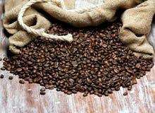 Geroosterde die koffiebonen uit de zak worden gemorst Stock Foto