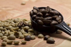 Geroosterde en niet geroosterde koffiebonen op een jeneverbessenplak Stock Foto