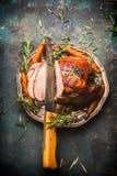 Geroosterde gesneden varkensvleesham met van het keukenmes en braadstuk groenten op donkere rustieke achtergrond stock afbeeldingen