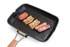 Geroosterde gestreepte bacon en worsten op de grillpan stock foto's