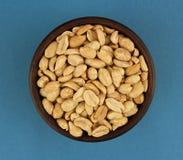 Geroosterde gezouten pinda's in kom op blauwe achtergrond, hoogste mening Royalty-vrije Stock Foto