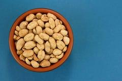 Geroosterde gezouten pinda's in kom op blauwe achtergrond, hoogste mening Stock Afbeelding