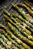 Geroosterde groene asperge met de toevoeging van parmezaanse kaaskaas, knoflook en aromatische kruiden op de grillplaat, royalty-vrije stock foto's