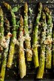 Geroosterde groene asperge met de toevoeging van parmezaanse kaaskaas, knoflook en aromatische kruiden op de grillplaat, stock afbeeldingen