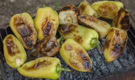 Geroosterde groene paprika's op hete sintels, geroosterde groente stock fotografie