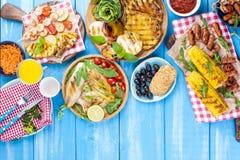 Geroosterde groenten, garnalen, fruit op een houten plaat en worsten, sap en salade op een blauwe achtergrond Het diner van de zo stock afbeelding