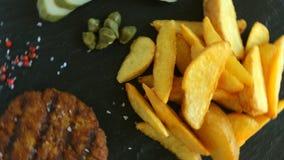Geroosterde hamburger met aardappels en ingelegde komkommersaus stock videobeelden
